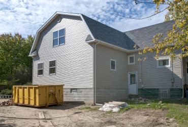 Home construction with gabled roof design and trash receptacle